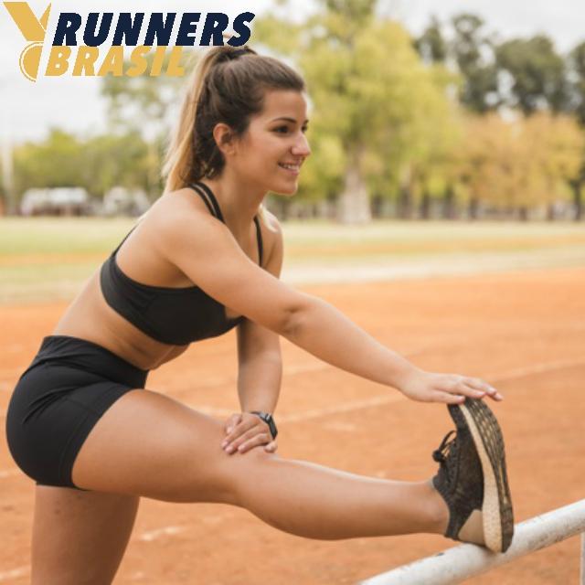 mulher-desportiva-estendendo-se-na-pista-do-estadio_23-2148173564